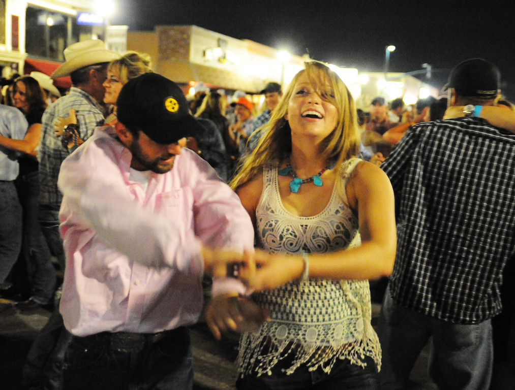 Jeremy Blazek, left, and Taylor Rieniets dance to the music during the Sheridan WYO Rodeo Street Dance Saturday night on Main Street. The Sheridan Press|Justin Sheely.