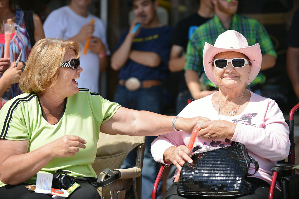 Gayla Merman, left, shares a laugh with her mother Arlene Colins after struggling to open a frozen popsicle treat during the 2014 Sheridan WYO Rodeo Parade Friday morning on Main Street. The Sheridan Press|Justin Sheely.