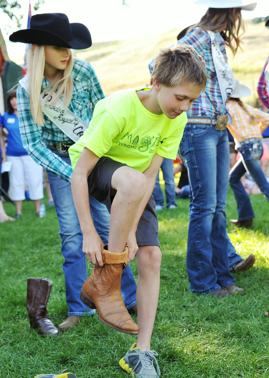10-year-old Norton McFadden slips on a boot for his turn at the annual Sheridan-Wyo-Rodeo Boot Kick-off Tuesday afternoon at Kendrick Park.