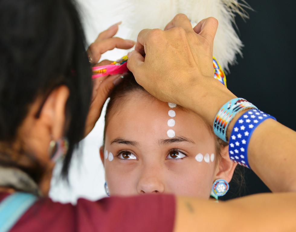 Twelve-year-old Dani Hardesty of Sheridan looks up as Kim Crawford adjusts her headdress during the Powwow Tuesday at the historic Sheridan Inn. The Sheridan Press|Justin Sheely