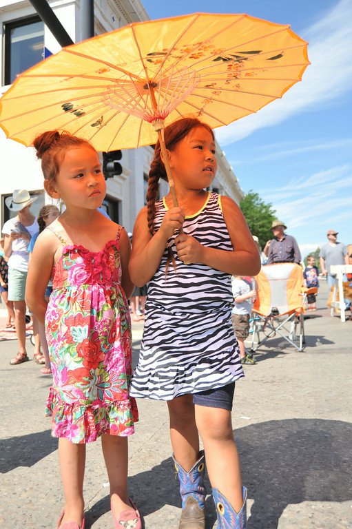 Theree-year-old Bonita Limpy, left, and Diana Old Elk, 5, watch from the shade of an umbrella during the 2014 Sheridan WYO Rodeo Parade Friday morning on Main Street. The Sheridan Press|Justin Sheely.