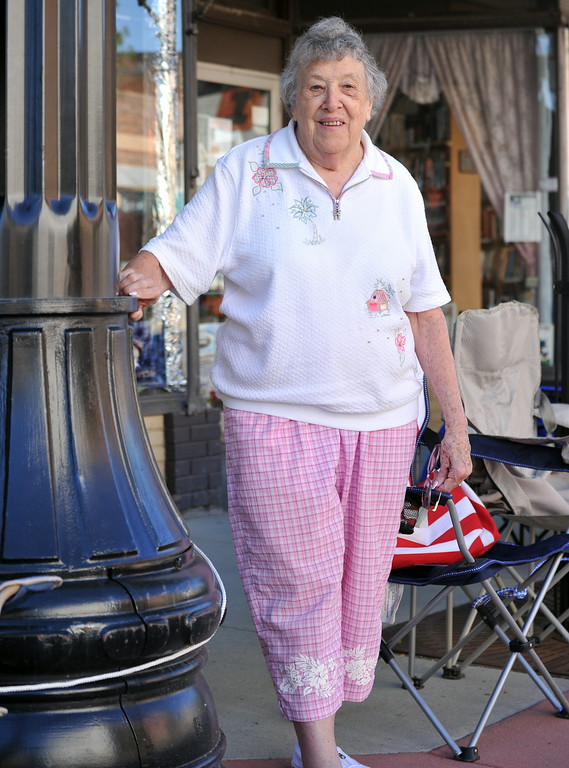 Mary Dowling of Sheridan stands on Main Street and watches the runners of the Sneakers and Spurs Rodeo 5K as they head for the finish line. The Sheridan Press|Mike Pruden