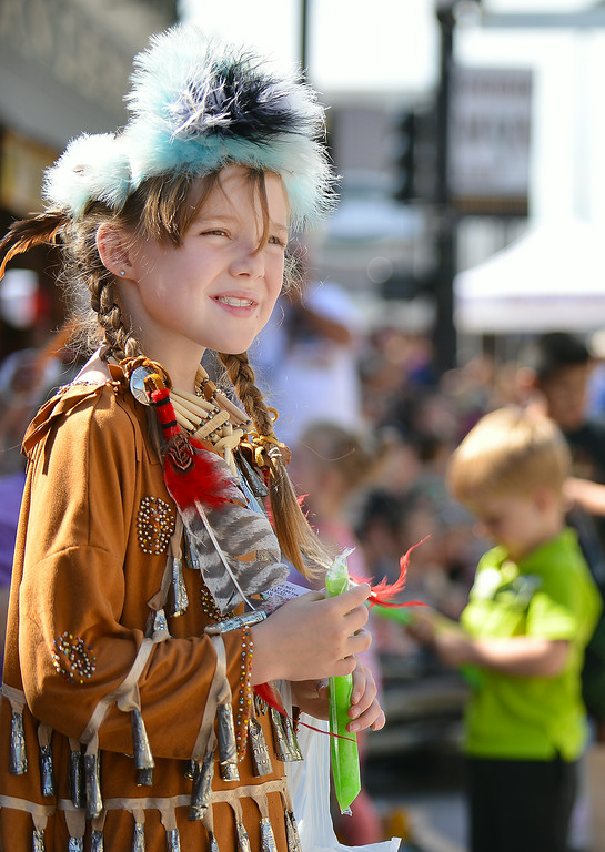 Nine-year-old Elizabeth DeTavernier watches parade floats pass her by during the 2014 Sheridan WYO Rodeo Parade Friday morning on Main Street. The Sheridan Press|Justin Sheely.