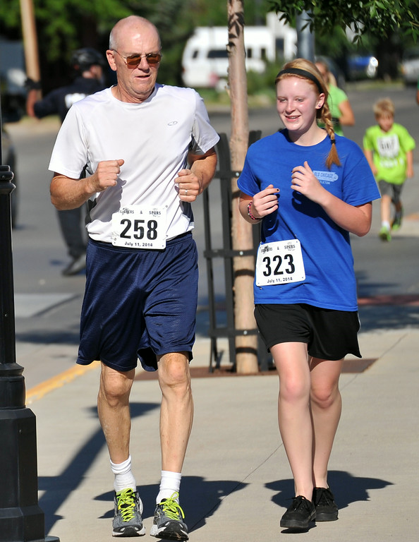 Ron Kaspzyk, left, and Cheyenne Noffsinger jog next to each during the Sneakers and Spurs Rodeo 5K on Friday in downtown Sheridan. The Sheridan Press|Mike Pruden