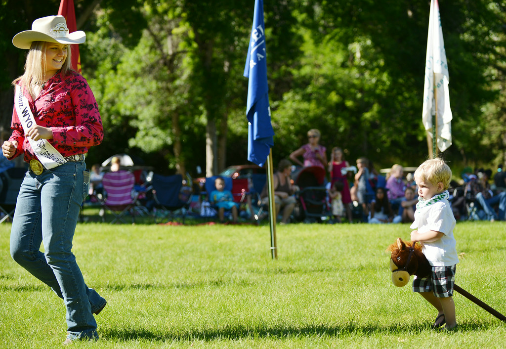 Senior Rodeo Princess Jackie Lewis leads Mason Brewer, 2, in the stick horse race during the annual Sheridan-Wyo-Rodeo Boot Kick-off Tuesday afternoon at Kendrick Park.