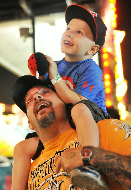 Four-year-old Dyllan Cope watches from the safety of his father Darren Cope's shoulders as his older siblings scream from a carnival ride Saturday night at the Sheridan County Fairgrounds arena. The Sheridan Press|Justin Sheely.
