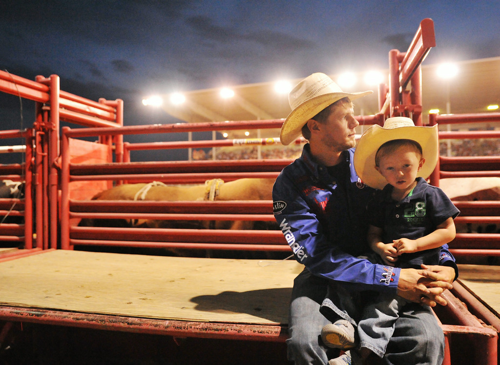 Kanin Asay of Powell, Wyoming, holds his two-year-old son Kasen Asay behind the chutes loaded with bulls for the bull riding event Wednesday night during the Sheridan WYO Rodeo. Asay was bumped out of the competition in Sheridan, but showed good sportsmanship by staying to pull ropes and support his friend in bull riding. The Sheridan Press|Justin Sheely.