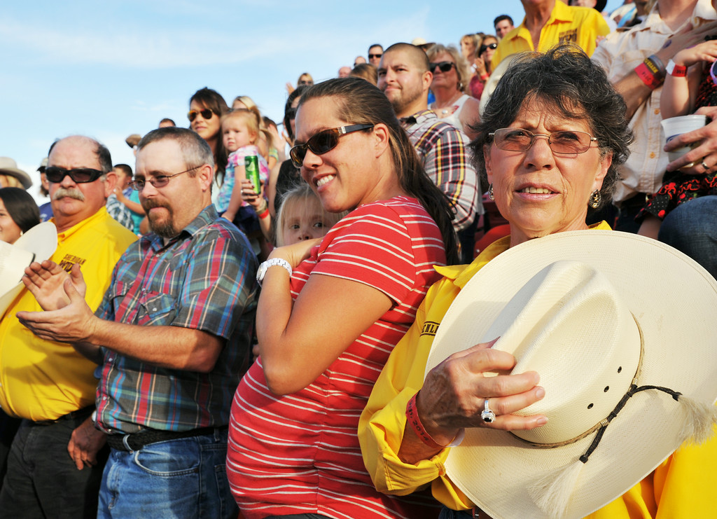 Judy Washut, right, holds her hat after the announcer finishes a prayer opening the first night of the Sheridan WYO Rodeo Wednesday in the Gold Buckle seating area at the Sheridan County Fairgrounds. The Sheridan Press|Justin Sheely.  (Next to Washut, Brian Barks, left, and Toni Barks)