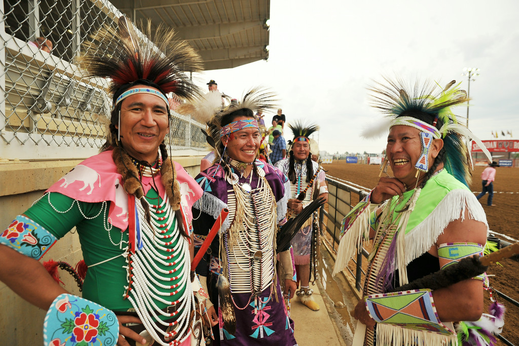 Native American powwow dancers, from left, Edgar Pretty On Top, Prinz Three Irons, and John Old Dwarf stand in the pit as the others prepare to enter the arena floor for a pre-show dance Friday night during the Sheridan WYO Rodeo at the Sheridan County Fairgrounds.