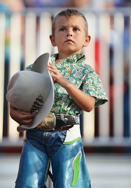 Four-year-old Kolby Smith holds his hat as riders enter the arena floor carrying national flags during the first night of the Sheridan WYO Rodeo Wednesday at the Sheridan County Fairgrounds. The Sheridan Press|Justin Sheely.