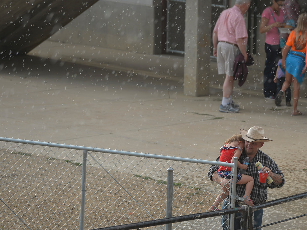 Justin Sheely | The Sheridan Press<br /> Rodeo goers seek cover from a passing rainstorm prior to the Sheridan County Rodeo Friday evening at the Sheridan County Fairgrounds.