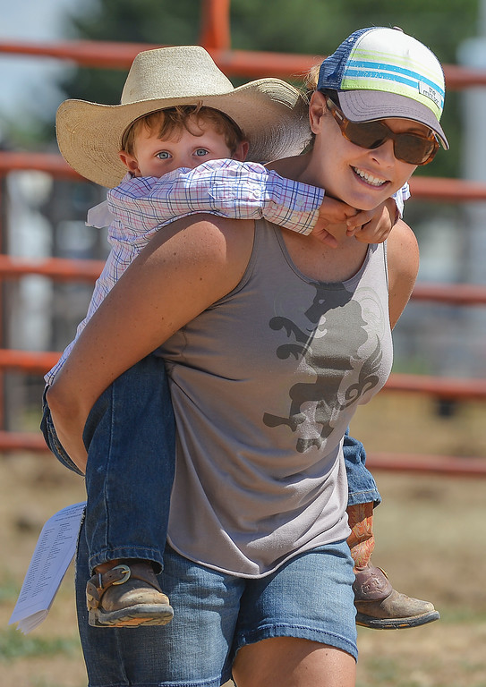 Justin Sheely | The Sheridan Press<br /> Four-year-old Tru Anesi gets a piggy-back ride from Jill Jarrard during the Saturday afternoon performance of the Sheridan County Rodeo at the Sheridan County Fairgrounds.