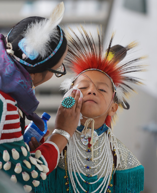 Justin Sheely | The Sheridan Press<br /> Six-year-old Blake Iron holds still as a his mother wipes off his face during the Crow Powwow Wednesday at the historic Sheridan Inn.