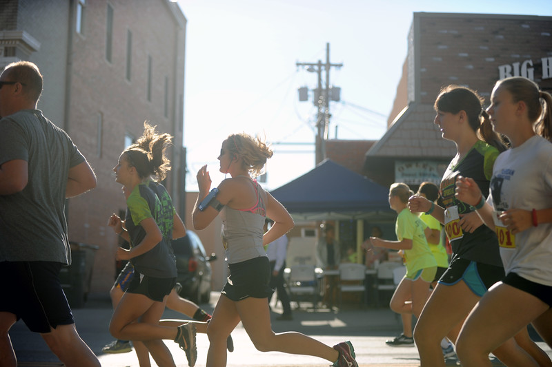 Mike Pruden | The Sheridan Press<br /> Runners jog past downtown storefronts during the Sneakers and Spurs race on Main Street in Sheridan.
