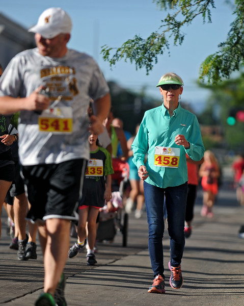 Mike Pruden | The Sheridan Press<br /> Rosey Wayman strolls down Main Street during the Sneakers and Spurs race in downtown Sheridan.