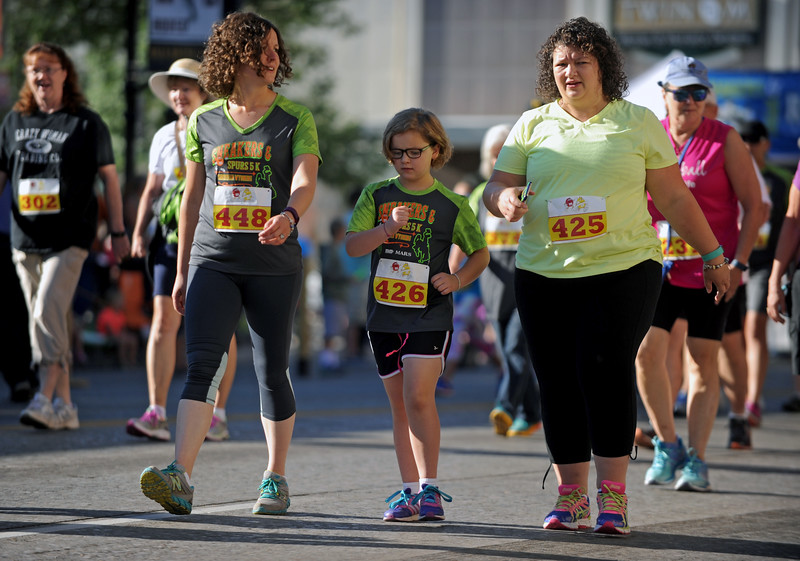 Mike Pruden | The Sheridan Press<br /> From left, Kristi Riggin, Fara Hayes and Donde Hayes chat as they walk down Main Street during the Sneakers and Spurs race in downtown Sheridan.