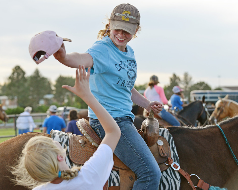 Twelve-year-old Sierra White plays keep away after grabbing her friend Lainey Konetzki's hat during the Sheridan Cowgirls Association Rodeo Thursday evening at the Sheridan County Fairgrounds.