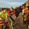 Twelve-year-old Shyan Davidson, left, and Lori Sigurdson unsaddle their horses after wrapping up a day at the Sheridan Cowgirls Association Rodeo Thursday evening at the Sheridan County Fairgrounds.