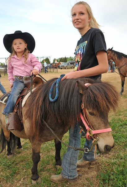 Four-year-old Mylee Kobold sits on a pony with Kade Koltiska during the Sheridan Cowgirls Association Rodeo Thursday evening at the Sheridan County Fairgrounds. Koltiska will be going to the National Junior High School Rodeo in Des Moines, Iowa, later this month.