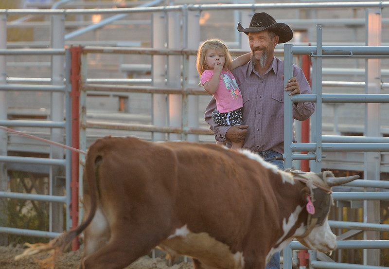 Justin Sheely | The Sheridan Press<br /> Cody Cunningham mans the gate for exiting steers with his granddaughter Carsyn Cates, 2, during slack at the Sheridan County Rodeo at the Sheridan County Fairgrounds Friday, Aug. 10, 2018.