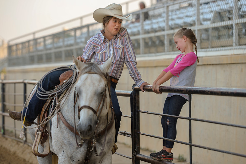 Justin Sheely | The Sheridan Press<br /> Seventeen-year-old Ellie Bard, left, visits with Acey Stalick, 6, during slack at the Sheridan County Rodeo at the Sheridan County Fairgrounds Friday, Aug. 10, 2018.