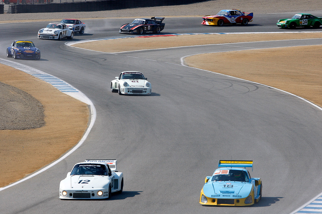 . Bruce Canepa (12) in his 1979 Porsche 935 and Zak Brown (18) in his 1981 Porsche 935 lead a group of racers in the Group 4A 1973-1981 FIA, IMSA, GT, GTX, AAGT class at Mazda Raceway Laguna Seca in Monterey during the Rolex Monterey Motorsports Reunion on Friday, Aug. 18, 2017.  (Vern Fisher - Monterey Herald)