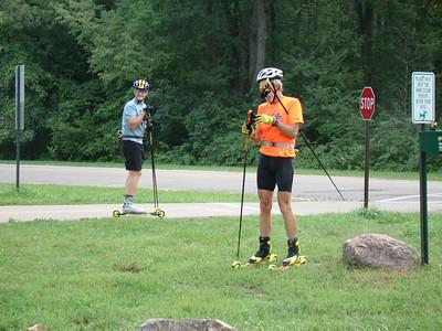 Bill Kaltz takes a quick break to loosen his ski boot. Doug Heady waits patiently.