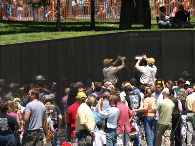 Rolling Thunder Motorcycle Rally, Washington, DC, May 25, 2008. Visitors crowd into the Vietnam War Memorial as a volunteer makes a wall rubbing.