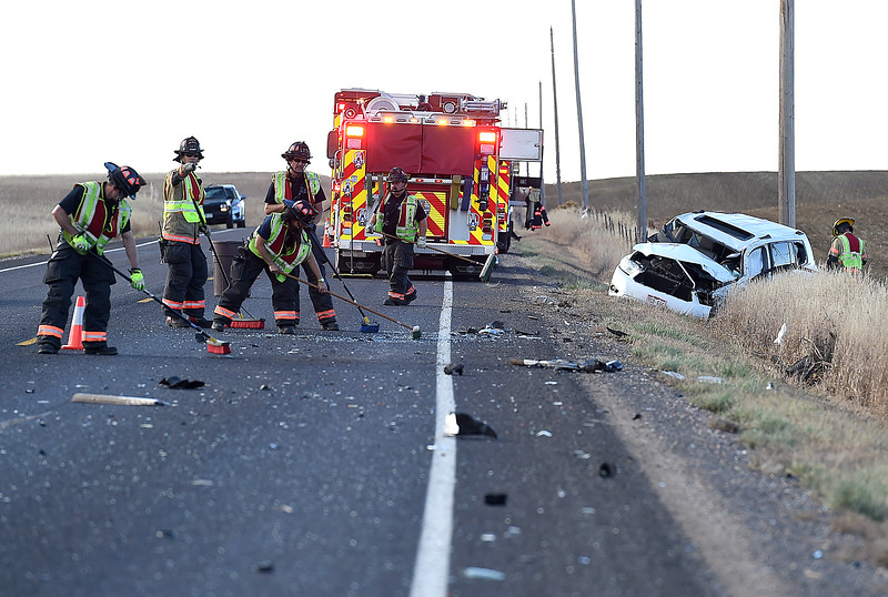 Loveland Fire Rescue Authority firefighters sweep debris after a rollover accident Thursday, Oct. 25, 2018, on Wilson Avenue north of 57th Street in north Loveland.  (Photo by Jenny Sparks/Loveland Reporter-Herald)