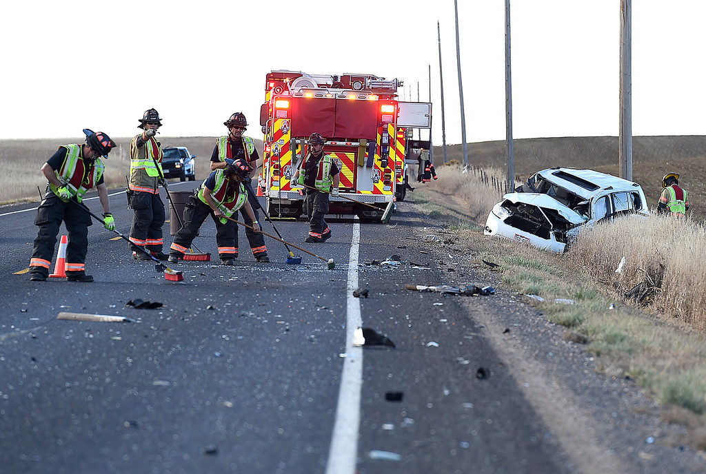 . Loveland Fire Rescue Authority firefighters sweep debris after a rollover accident Thursday, Oct. 25, 2018, on Wilson Avenue north of 57th Street in north Loveland.  (Photo by Jenny Sparks/Loveland Reporter-Herald)