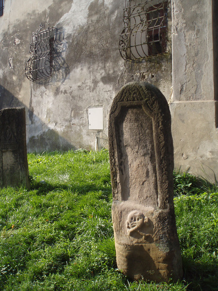 An appropriately weathered tombstone next to the church.