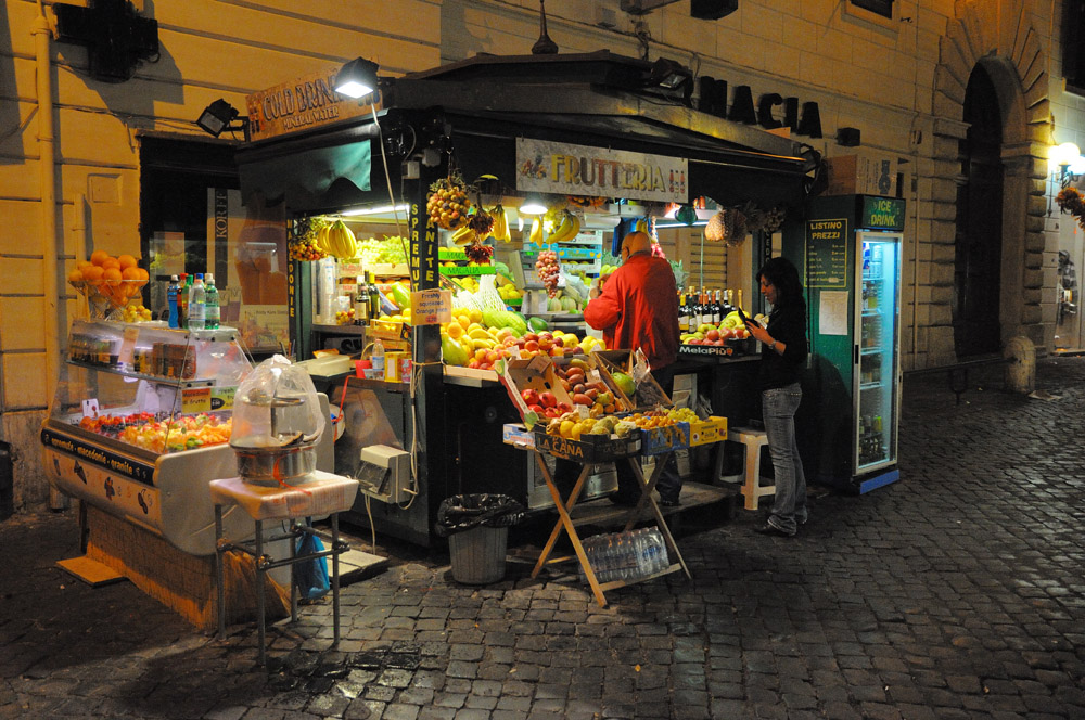 Fruit stand at night near Trevi Fountain.
