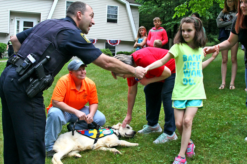 Pepperell police officer Fabrizio Vestri, shakes hands with 9 year old Olivia Twigg after he escorted her new service dog Romeo to her Pepperell home. Nashoba Valley Voice Photo by David H. Brow.