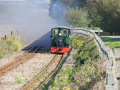 St. Egwin approaching the level crossing from the Hythe direction with one of the stopping shuttles to New Romney