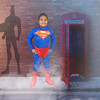 Little girl as superhero next to a telephone booth
