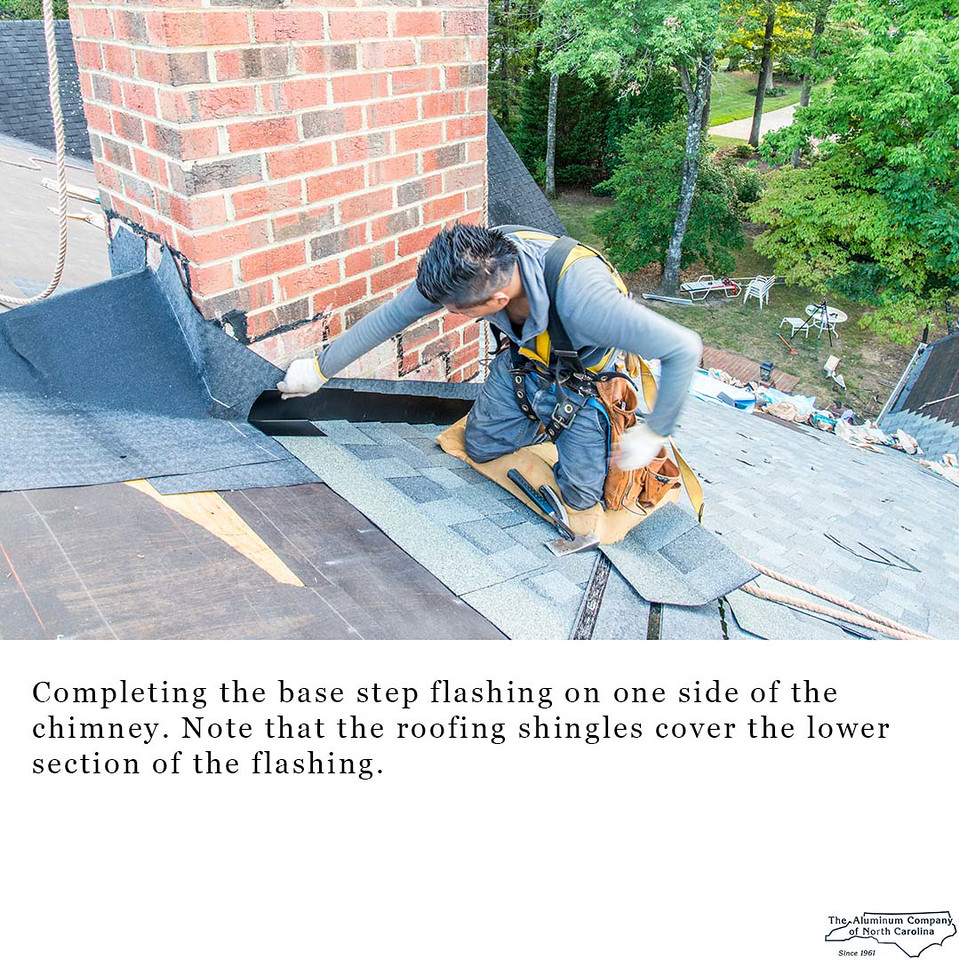 Completing the base step flashing on one side of the chimney. Note that the roofing shingles cover the lower section of the flashing.