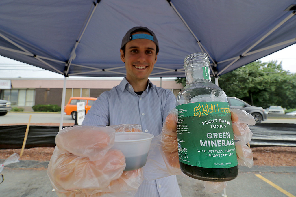 . Roots Market, Kitchen, Juice Bar and Yoga held its Rootsfest 2018 on Saturday, September 8, 2018 in Leominster. Wynter Griffin with Gold Thread Drinks shows of one of the drinks, Green Minerals, he had at his booth during the festival. He had samples for everyone to try. SENTINEL & ENTERPRISE/JOHN LOVE