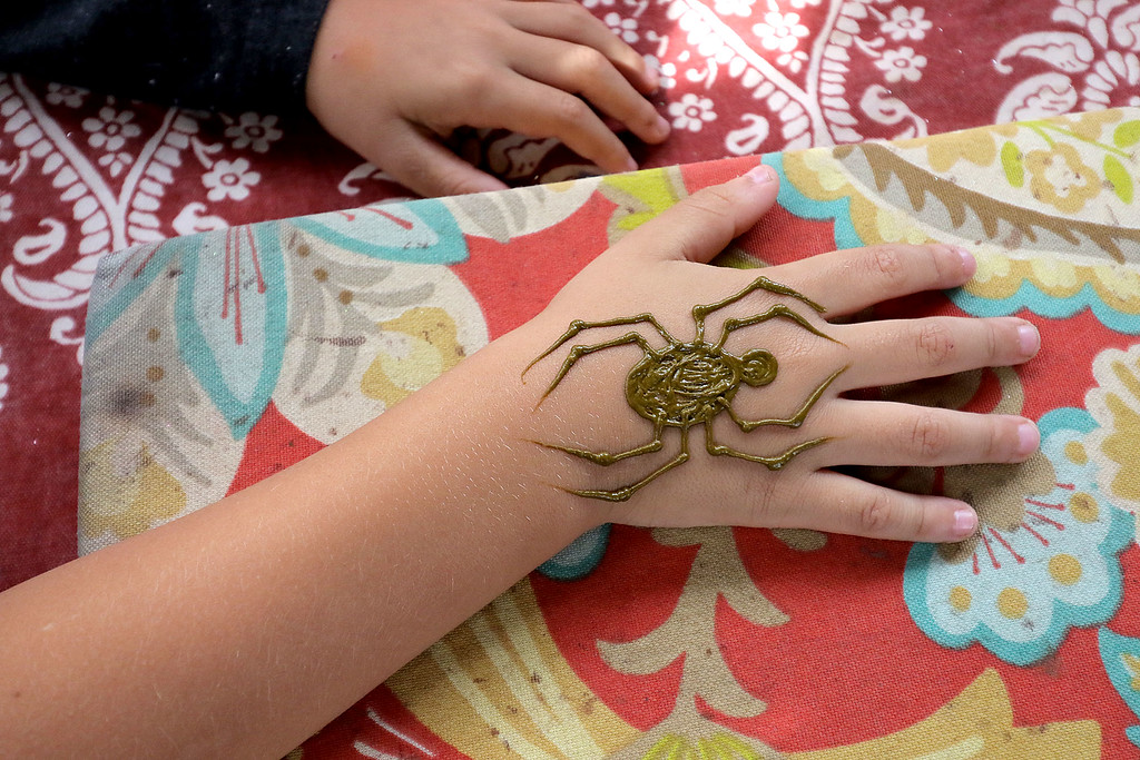 . Roots Market, Kitchen, Juice Bar and Yoga held its Rootsfest 2018 on Saturday, September 8, 2018 in Leominster. Dominic Sanchez, 6, of Worcester gets some henna in the shape of a spider from Mandy Roberge of Wicked Good Henna at her booth during the festival. SENTINEL & ENTERPRISE/JOHN LOVE