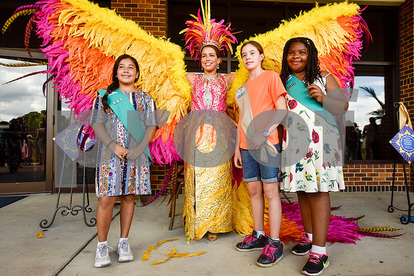 Girls scouts of Dallas Troop 712 Shyla Veliz, Ruby Simms and Chizi Okolo, all 10, pose for a photo with Sophie Aliece Hollis during the 84th Texas Rose Festival Queen's Tea at the Tyler Rose Garden in Tyler, Texas, on Saturday, Oct. 21, 2017. All the ladies and their escorts were in their full dress attire on the garden grounds to take photos with the community. (Chelsea Purgahn/Tyler Morning Telegraph)