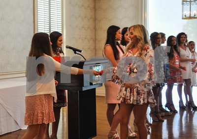 A Lady-in-Waiting receives a gift at the Friends of the Rose luncheon on Wednesday, July 11.  The luncheon is a way to welcome participants to practice week in preparation for the 85th Texas Rose Festival held in October. (Jessica T. Payne/Tyler Paper)