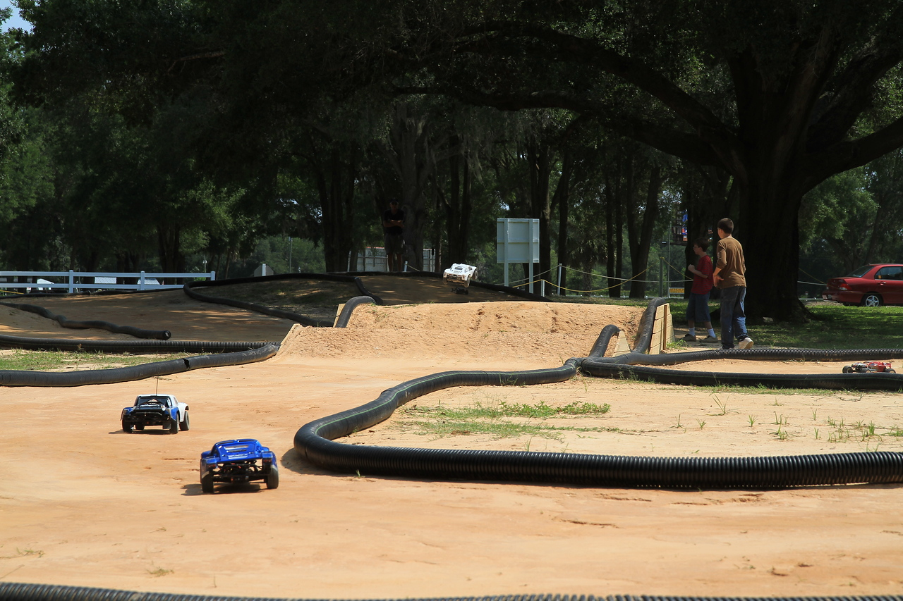 Note the white race car airborn over the two jumps ahead of the two coming thru the turn.
