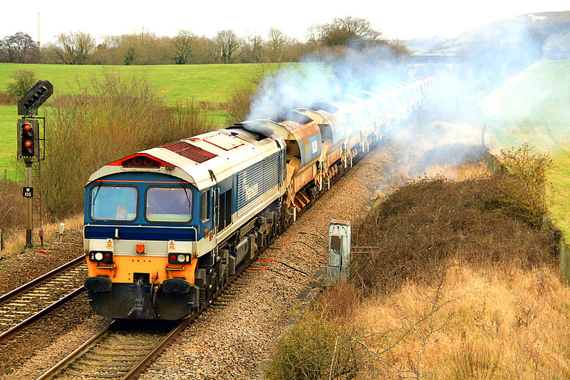 59104 makes a smokey departure from Westbury as it approaches Fairwood with 6W34, ballast for the East Somerset (Merehead and Cranmore) branch. Note the Westbury White Horse, just visible through the exhaust in the top right of the frame. 25/02/12.