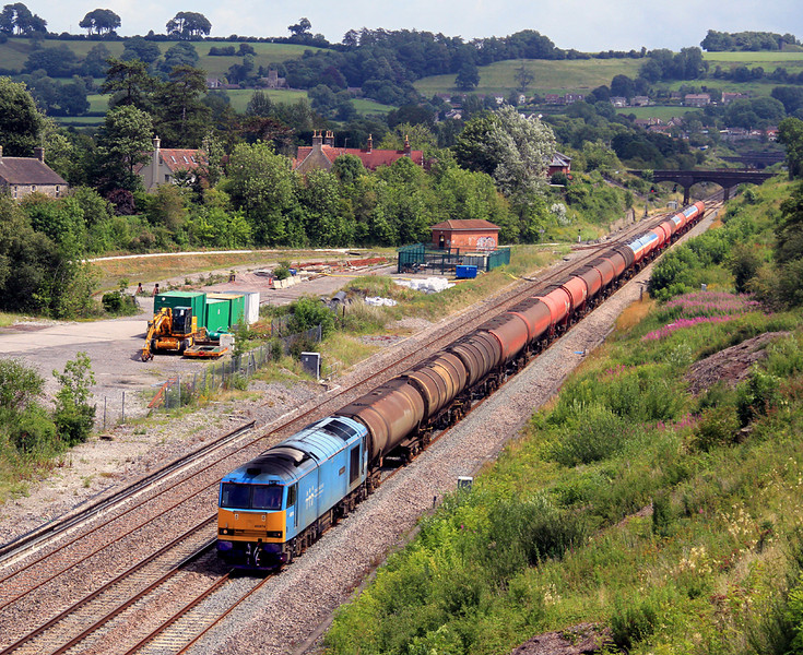 60074 'Teenage Spirit' thrums past the site of Chipping Sodbury station with 6B33, Theale to Margam empty fuel tanks on 9 July, 2011. The bridge used in the previous shots is behind the last wagon.  Unless you are over six feet tall, you will probably find a small step ladder helpful at this location to get a comfortable view over the bridge parapet.   To reach this location, take the residential street that heads south off the Chipping Sodbury roundabout and park in the housing estate.  Climb a style to reach a grassy footpath that crosses the bridge.