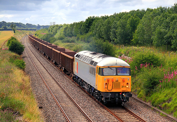A rare visitor made an appearance on 16 July 2011 in the shape of 56311 on a Cardiff Tidal Sidings to Hoo Junction empty scrap working.  The location is Farleaze, an overbridge carrying a private farm road over the line between Fosseway and Hullavington.