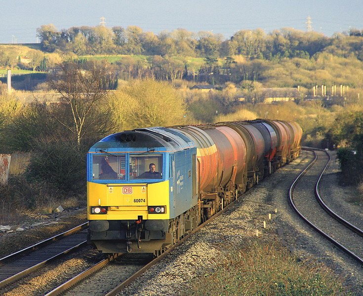 Catching the final rays of cold, winter, sun, 60074 'Teenage Spirit' approaches Pilning on 6 February 2013 with 6B33,  13:00 Theale to Robeston empty TEA bogie tanks.  This was taken from the footbridge on the little-used station at Pilning.