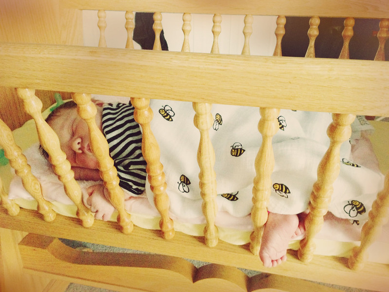 Sticking her feet through the bars on the cradle.
