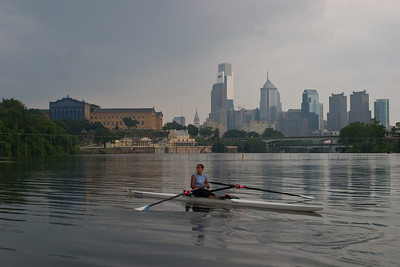Kiran rowing with the Art Museum behind her on the left and the Philadelphia skyline on the right.