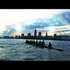 Cleveland State University's Mens Varsity Eight Rowing shell on Lake Erie with the City of Cleveland's skyline behind them.  To the Left is the browns stadium.  The biggest tower is Key Tower and the 2nd is Tower City.