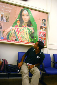 """Arshad Islam who is also affectionately called """"Coach Sahib"""" examining the poster in the waiting area."""