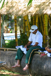 Zaheer sittin under a thatched roof between practices.